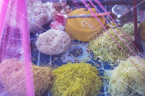 Various noodles under a net at a market in Myanmar