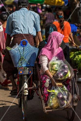 A Burmese woman with vegetables on a rickshaw (Myanmar)