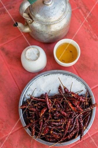 Dried chilli peppers, salt and tea on a table (Myanmar)