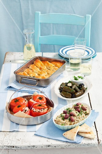 Various Greek appetisers: dolmadakia, tomatoes stuffed with rice, spanakopita, aubergine dip with olives