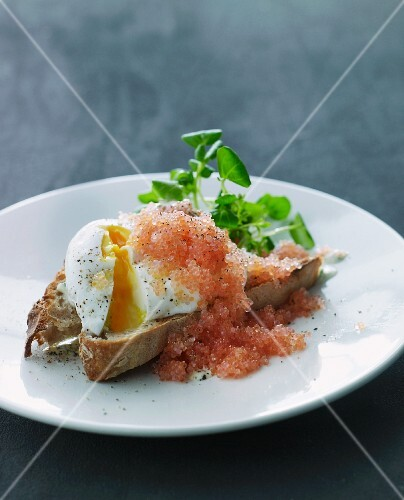 A slice of bread topped with a poached egg and caviar