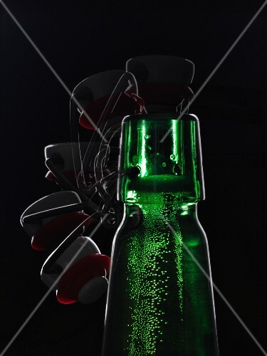 A green beer bottle with a flip-top lid backlit against a black background being opened (multiple expose)