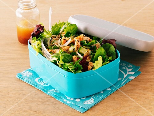 Mixed leaf salad with smoked salmon in a lunch box with a jar of dressing