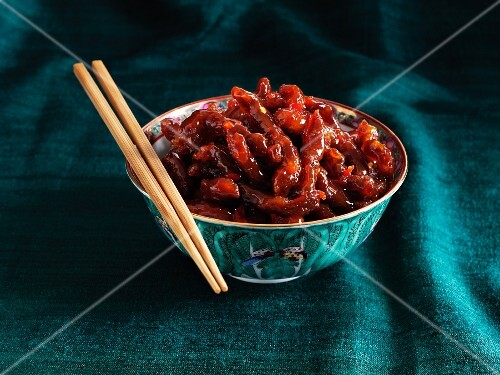 Crispy beef strips with chilli in an oriental bowls with chopsticks