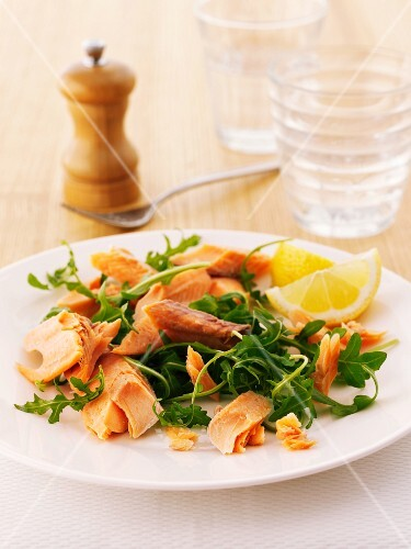 Smoked trout and rocket salad garnished with a lemon wedge