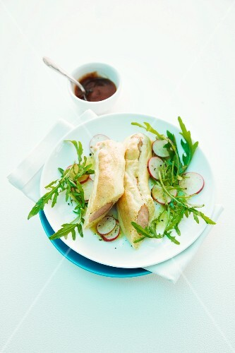 Sausages in puff pastry with rocket and radishes