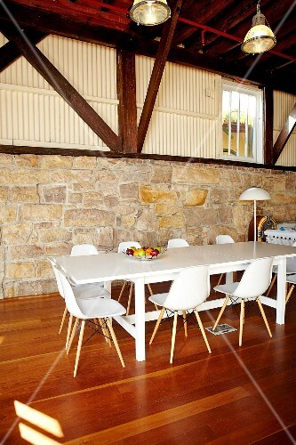 A dining area with white bucket chairs in a hall-like living room with a half-height natural stone wall and visible roof beams