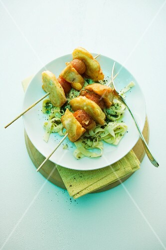 Turkey skewers with sausage on tagliatelle