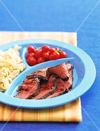 Beef steak with cherry tomatoes and pasta