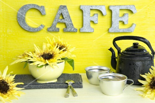 An old coffee jug, aluminium cups and sunflowers