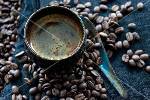 A coffee cup on coffee beans with a rusty spoon