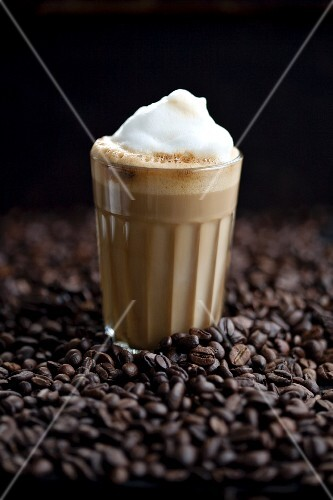 A glass of latte macchiato on coffee beans