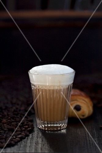 A latte macchiato, chocolate croissant and coffee beans