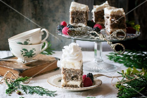 Two tea cups and a poppy seed cake with cream cheese, cream and berries