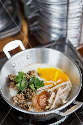 A Thai breakfast featuring fried egg and pork, Thailand