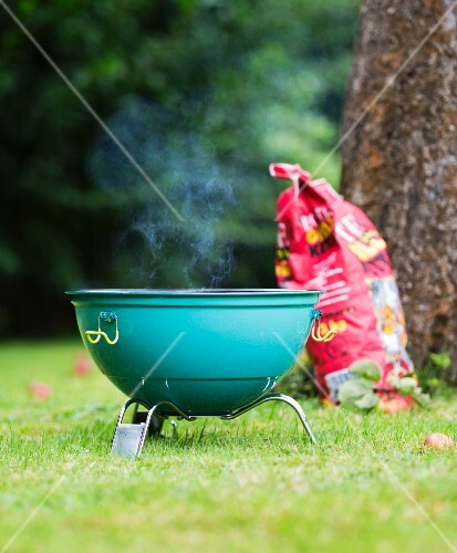 A smoking barbecue with a sack of coal in a field