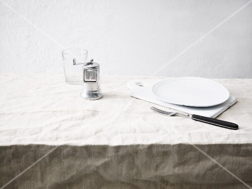 A plate, fork, pepper shaker and a glass