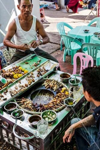 Men selling skewers at a market in Myanmar