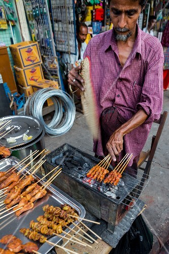 A Burmese man grilling at a market in Myanmar