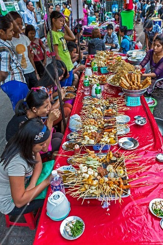 Burmese people eating satay dishes at a street bar in Myanmar