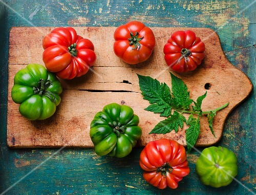 Green and red beefsteak tomatoes with leaves on a chopping board