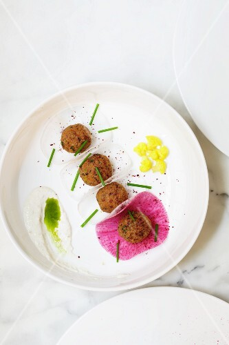Falafel on slices of radish (seen from above)
