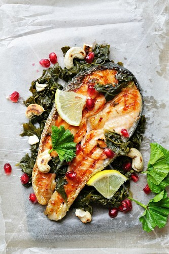 Fried salmon steak with lemon and pomegranate seeds