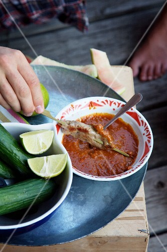 A satay skewer being dipped into sauce