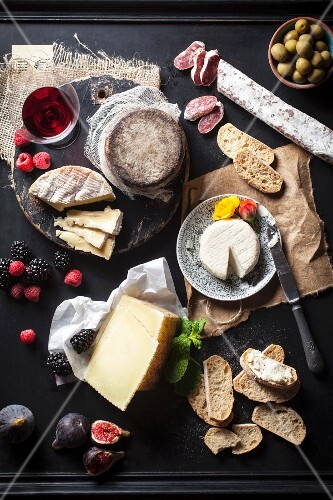 An arrangement of cheese also featuring fruit, salami, bread, olives and wine