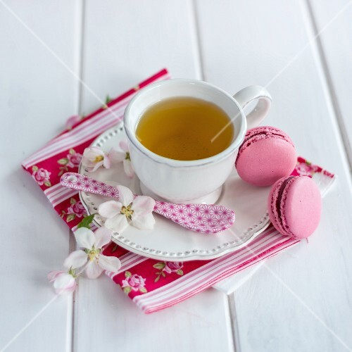A cup of tea with two macaroons