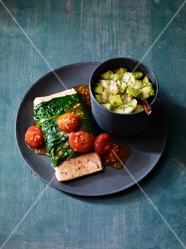 Salmon wrapped in spinach served with tomatoes