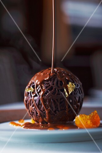 An artistic chocolate ball with gold leaf and chocolate sauce