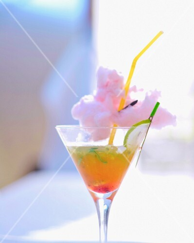 A cocktail garnished with candy floss