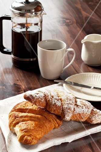 Chocolate and cinnamon croissants and a cup of black coffee