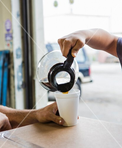 A worker pouring a cup in a of coffee in department store