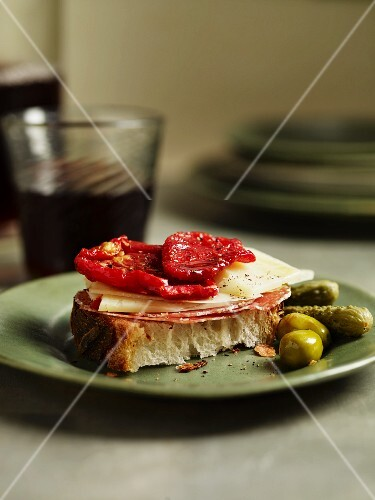 A slice of bread topped with salami, cheese and dried tomatoes