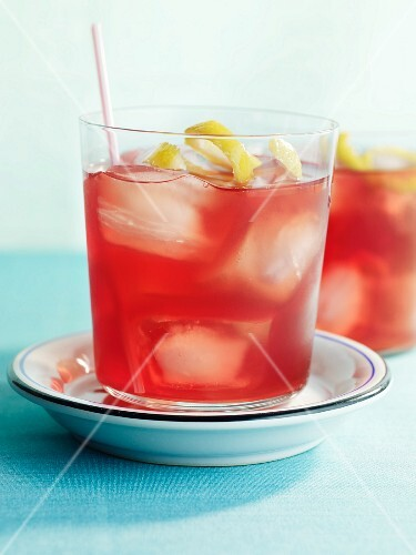 Cranberry drink with ice cubes and lemon zest