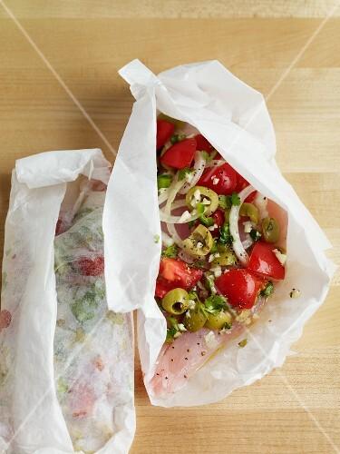 Fischfilet mit Tomaten, Oliven und Zwiebeln im Pergamentpapier