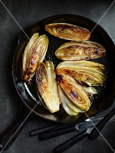 Fried chicory halves in a pan