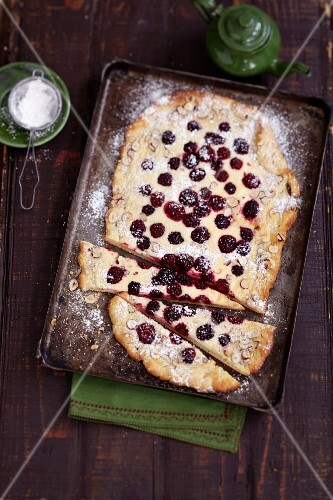 Blackberry and sour cream flan dusted with icing sugar on an old baking tray