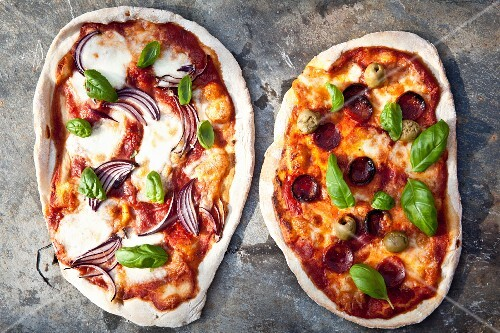 Two stone oven pizza with onions, salami and olives