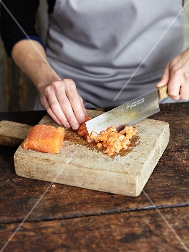 Raw fish fillet being chopped with an oriental knife