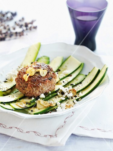 A minced meat steak with garlic on a courgette salad