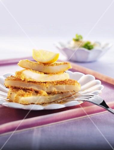 Breaded celeriac escalopes with a lemon wedge