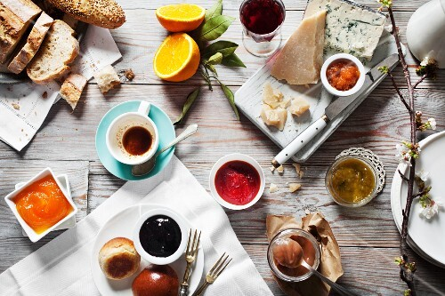Various types of jam with cheese, bread and drinks on a wooden table