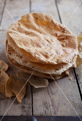 A stack of poppadoms on a wooden table