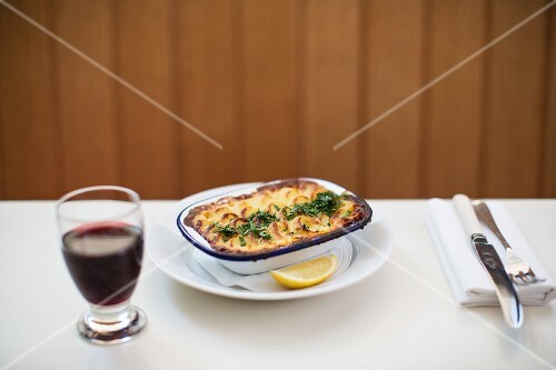 Shepherd's pie in a baking dish with a glass of red wine