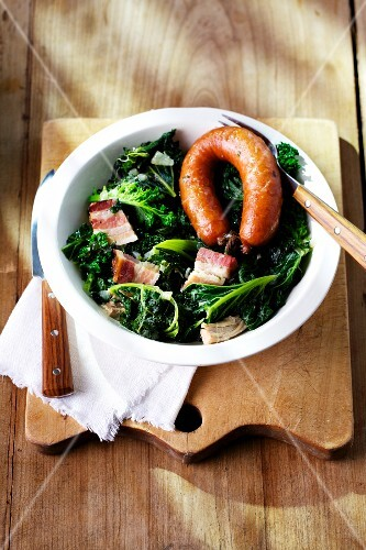 Green kale with Pinkel (smoked sausage from bacon, groats and spices) on a plate