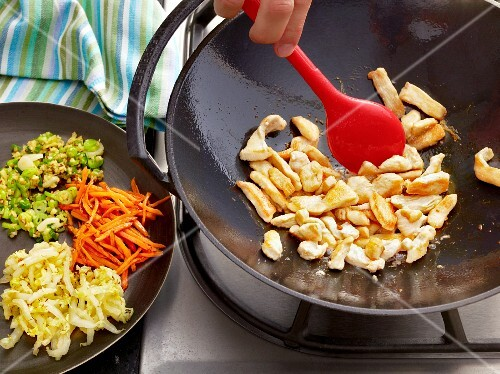 Bami Goreng being made: chicken breast being fried in a wok