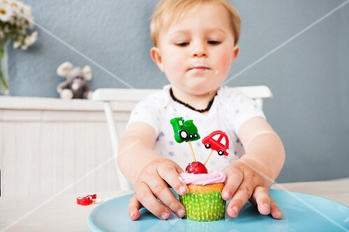 A little boy playing with a cupcake at a table